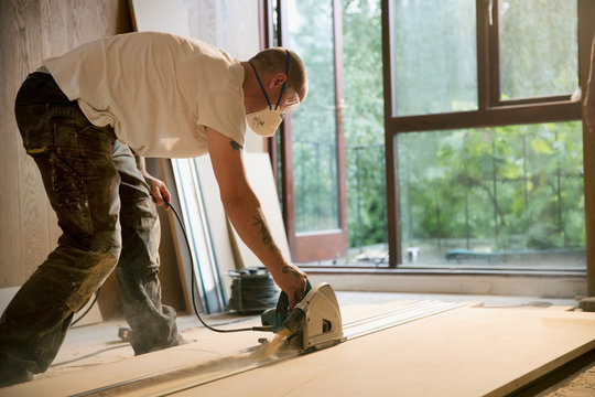 Construction worker using electric saw to cut wood board in house