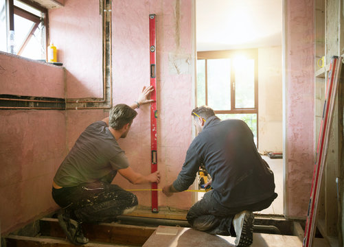 Construction workers using level too and tape measure in house