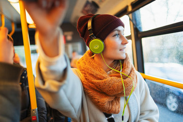 Young woman in stocking cap and scarf listening to music with headphones on bus