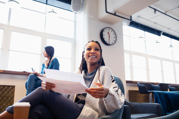 Happy, confident businesswoman with paperwork in office