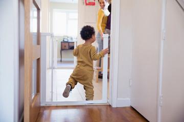 Cute baby boy balancing in doorway