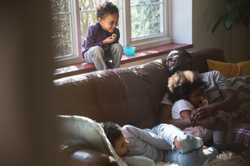 Happy father and children cuddling on living room sofa