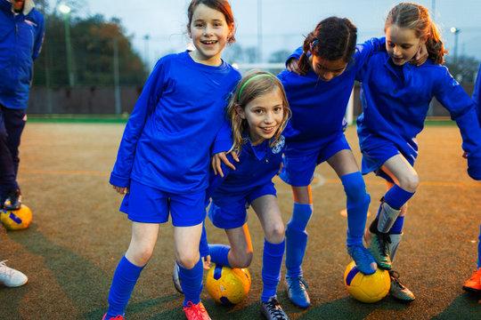 Portrait happy girls soccer team on field