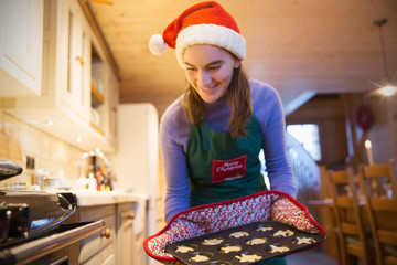 Smiling teenage girl in Christmas apron and Santa hat baking muffins in kitchen