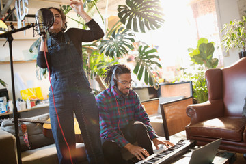 Young man and woman recording music, singing and playing piano in apartment