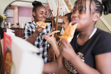 Tween girls enjoying pizza