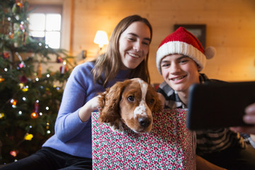 Brother and sister taking selfie with dog in Christmas gift box