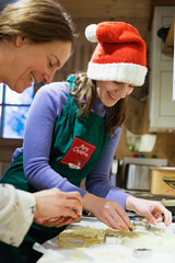 Mother and daughter in Christmas apron and Santa hat baking in kitchen