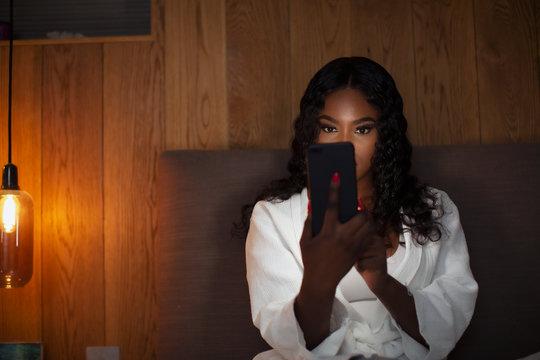 Young woman using smart phone in dark bedroom