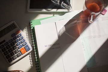 Retirement portfolio on sunny table with tea and calculator