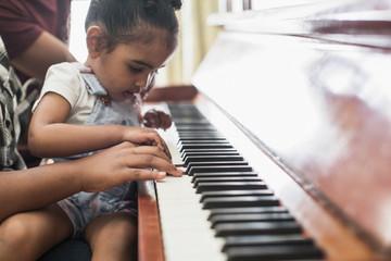 Curious toddler girl playing piano