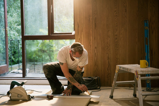 Construction worker measuring wood board in house