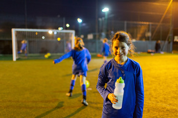Portrait smiling girl soccer player drinking water on field at night