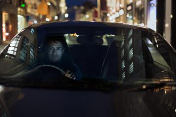 Portrait man driving car at night