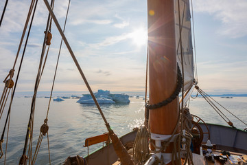 Ship sailing toward icebergs on sunny tranquil Atlantic Ocean Greenland