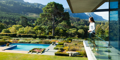 Woman standing on sunny, luxury balcony overlooking swimming pool and landscape, Cape Town, South Africa