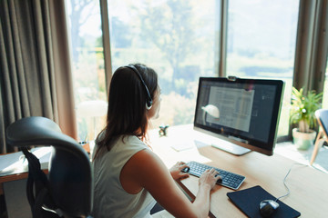 Businesswoman with headset working at computer in home office