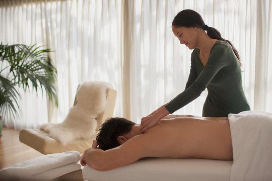 Female masseuse giving man massage