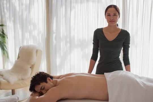Portrait confident female masseuse giving man massage