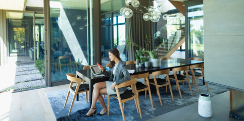 Businesswoman working from home, using smart phone at modern dining table