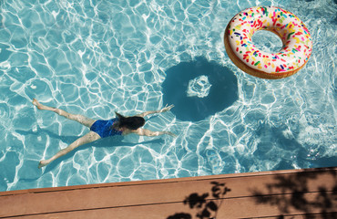 Girl swimming underwater in sunny swimming pool