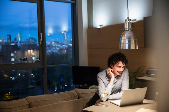 Man using laptop and drinking white wine in urban apartment at night