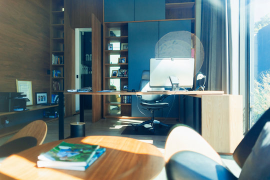 Computer on desk in sunny, modern home office