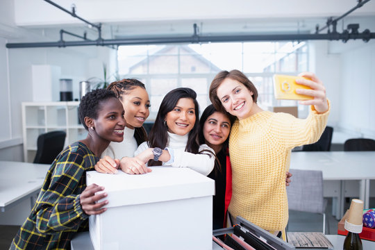 Businesswomen moving into new office, taking selfie