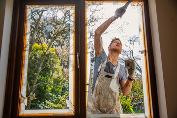 Male painter painting home exterior window trim