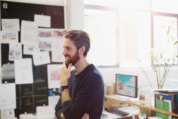 Happy creative businessman rubbing beard in office