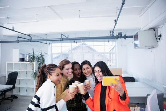 Businesswomen celebrating new office, taking selfie