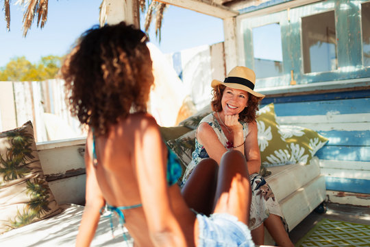 Happy mother and adult daughter talking, relaxing on beach hut patio