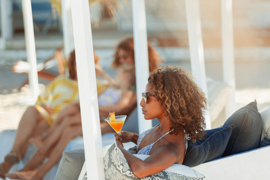Young woman relaxing with cocktail on beach patio