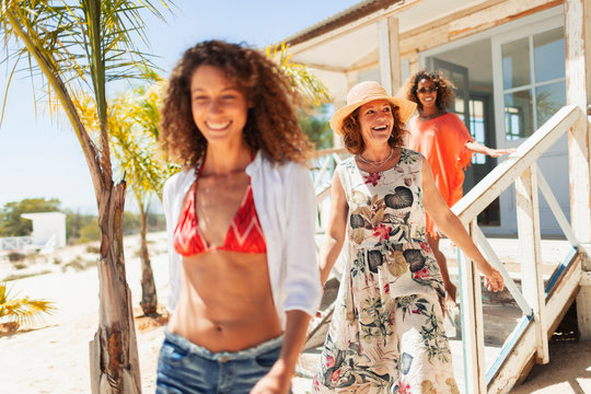 Mother and adult daughters leaving sunny beach hut