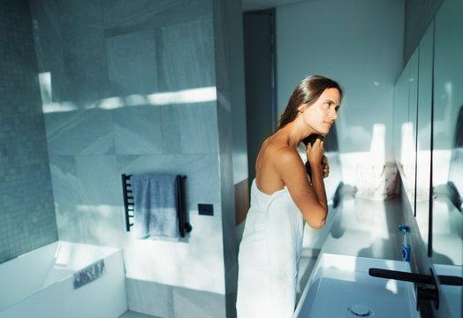 Woman wrapped in towel brushing hair in modern bathroom
