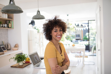 Portrait happy young woman in kitchen