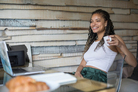 Happy young woman drinking coffee at laptop in home office