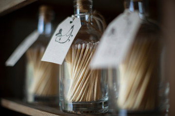 Close up matchstick bottles with bird labels on retail shelf