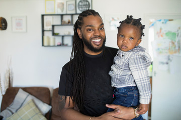 Portrait happy father with long braids holding toddler son