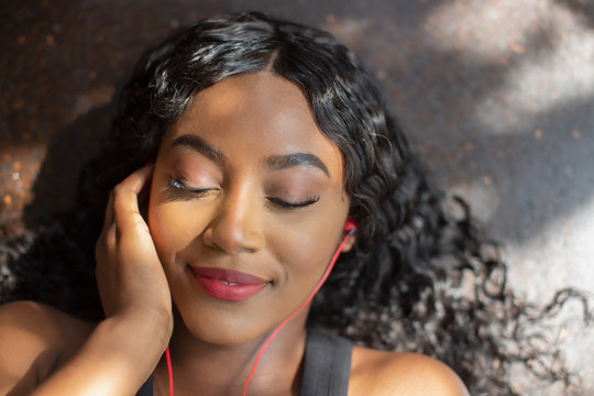 Serene young woman listening to music with headphones