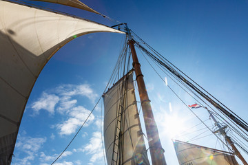 Wooden and mast and sailboat sails below sunny blue sky