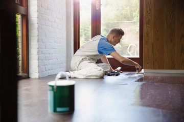 Focused young male construction worker laminating floors at construction site