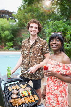 Portrait happy young multiethnic couple barbecuing at poolside