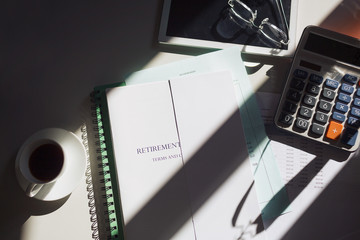 Retirement portfolio on sunny table with coffee and calculator