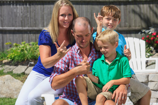 Family with hearing impairments signing