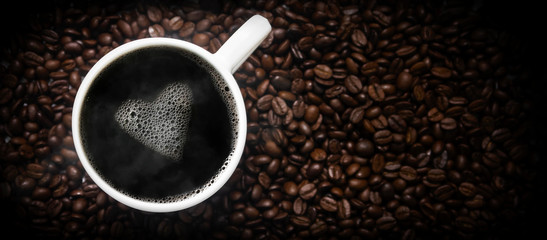 cup of hot coffee on coffee beans with a heart of foam