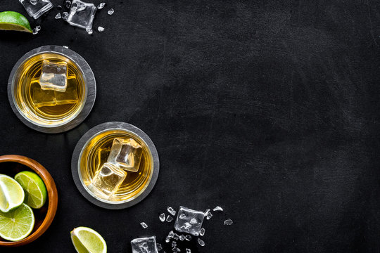 Bar background with whiskey and ice on black desk top-down frame copy space