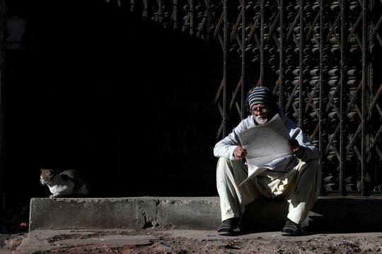Rafiq, a labourer, sits beside cat as he reads newspaper in sunlight in Karachi