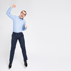 portrait of cheerful young handsome businessman celebrating something and jumping over gray...