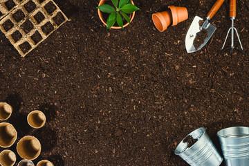 Foto op Plexiglas Tuin Gardening tools on soil texture background top view.